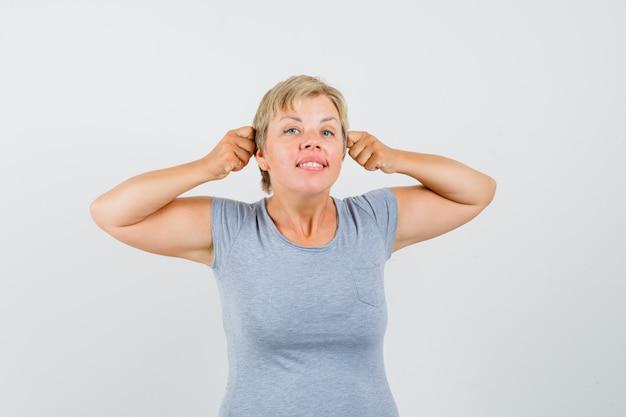 Blonde vrouw die haar gebalde vuisten aan oor in lichtblauw t-shirt drukt en gelukkig, vooraanzicht kijkt.