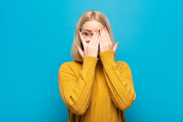 Blonde vrouw die haar gezicht bedekt met handen, tussen de vingers gluurt met een verbaasde uitdrukking en opzij kijkt
