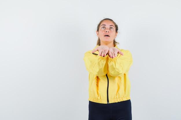 Blonde vrouw die handen uitrekt als iets denkbeeldigs vasthoudt in geel bomberjack en zwarte broek en gefocust kijkt