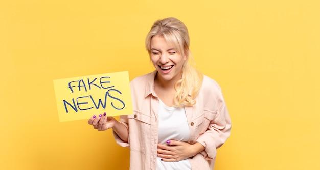 Blonde vrouw die hardop lacht om een of andere hilarische grap, zich gelukkig en opgewekt voelt, plezier heeft