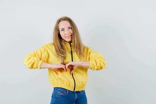 Blonde vrouw die hartgebaar in jasje, jeans toont en vrolijk kijkt.