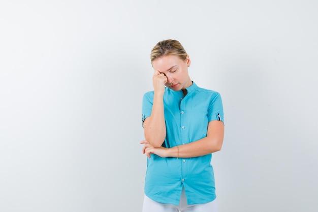 Blonde vrouw die hoofd naar beneden buigt in blauwe blouse en er verontrust geïsoleerd uitziet