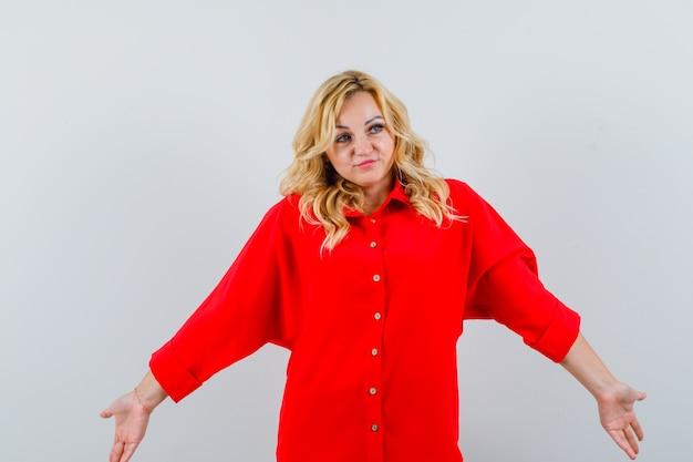Blonde vrouw die hulpeloos gebaar toont, weg kijkt in rode blouse en peinzend, vooraanzicht kijkt.