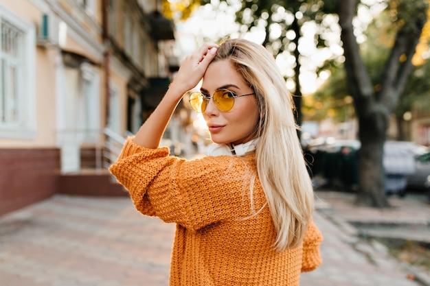 Blonde vrouw die in bruine gebreide sweater over schouder met leuke glimlach kijkt