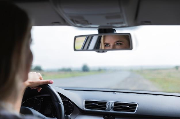 Blonde vrouw die in de achteruitkijkspiegel kijkt