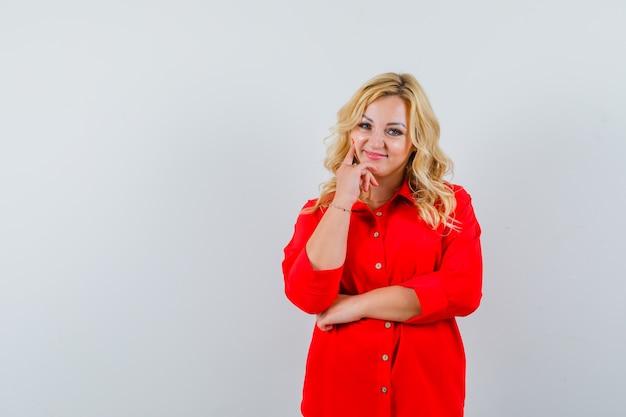 Blonde vrouw die in rode blouse wijsvinger op wang zet en mooi, vooraanzicht kijkt.