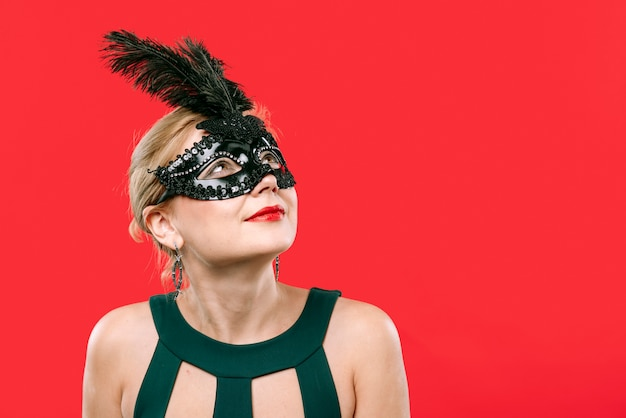 Blonde vrouw die in zwart carnaval masker omhoog kijkt