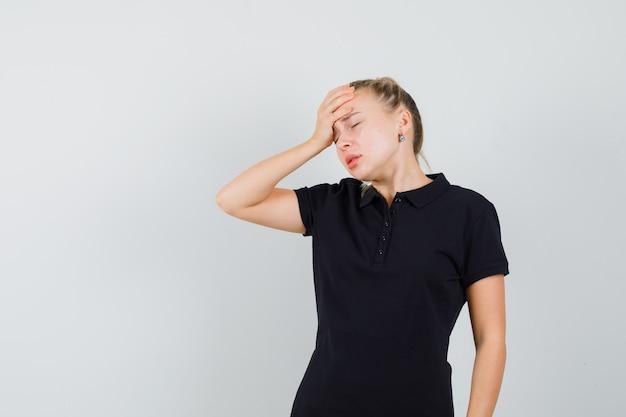 Blonde vrouw die in zwart t-shirt haar hand op haar hoofd legt en geïrriteerd kijkt