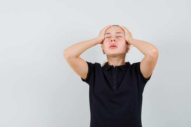 Blonde vrouw die in zwart t-shirt haar hoofd met beide handen houdt en uitgeput kijkt
