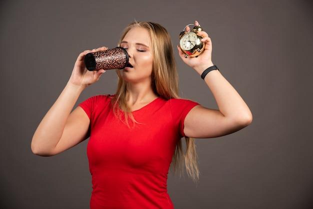 Blonde vrouw die koffie drinkt terwijl ze de klok vasthoudt.