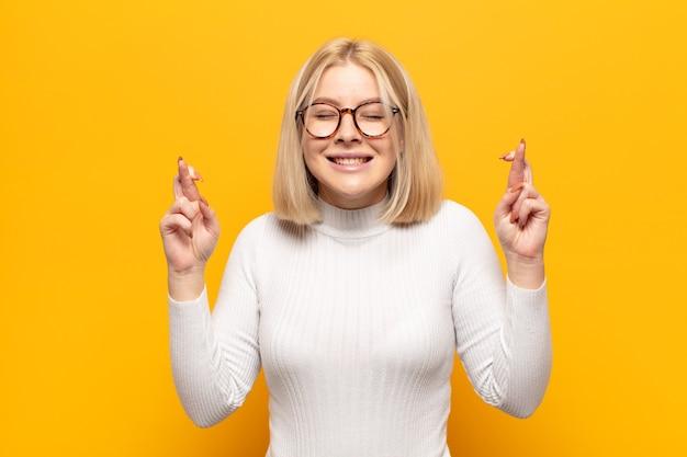 Blonde vrouw die lacht en angstig beide vingers kruist, zich zorgen maakt en geluk wenst of hoopt