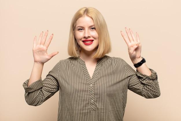 Blonde vrouw die lacht en er vriendelijk uitziet, nummer negen of negende toont met de hand naar voren, aftellend