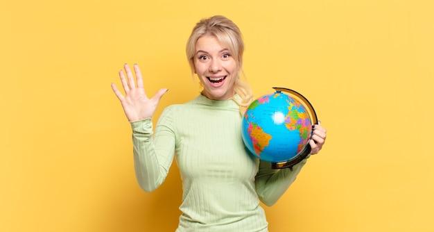 Blonde vrouw die lacht en er vriendelijk uitziet, nummer vijf of vijfde toont met de hand naar voren, aftellend