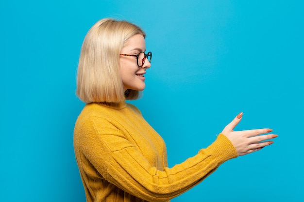 Blonde vrouw die lacht, je begroet en een hand schudt om een succesvolle deal te sluiten
