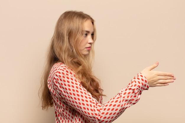 Blonde vrouw die lacht, u begroet en een handschud aanbiedt om een succesvolle deal, samenwerkingsconcept te sluiten