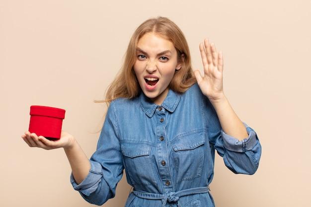 Blonde vrouw die met handen in de lucht gilt, zich woedend, gefrustreerd, gestrest en boos voelt