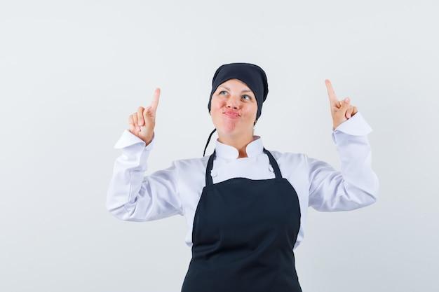 Blonde vrouw die met wijsvingers omhoog wijst, lippen in zwart kookuniform buigt en er mooi uitziet