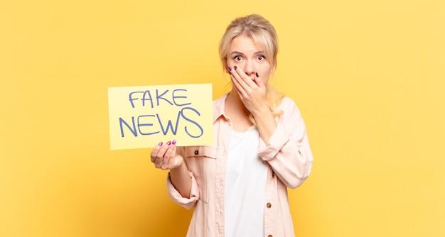 Blonde vrouw die mond bedekt met handen met een geschokte, verbaasde uitdrukking, een geheim bewaren of oeps zeggen