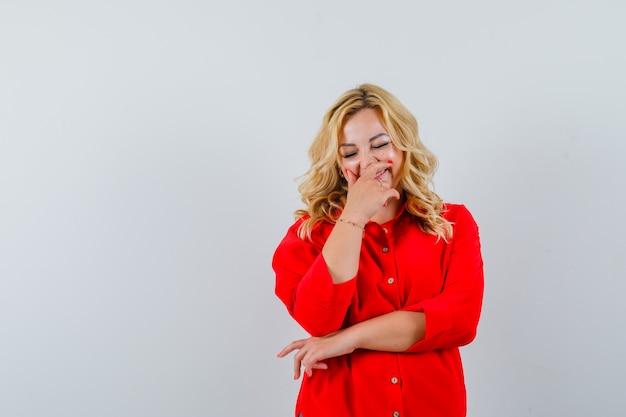 Blonde vrouw die mond behandelt met handen, die in rode blouse glimlacht en gelukkig kijkt