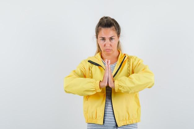 Blonde vrouw die namaste-gebaar in geel bomberjack en gestreept overhemd toont en ontspannen kijkt