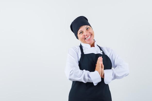 Blonde vrouw die namaste-gebaar in zwarte uniforme kok toont en er mooi uitziet. vooraanzicht.