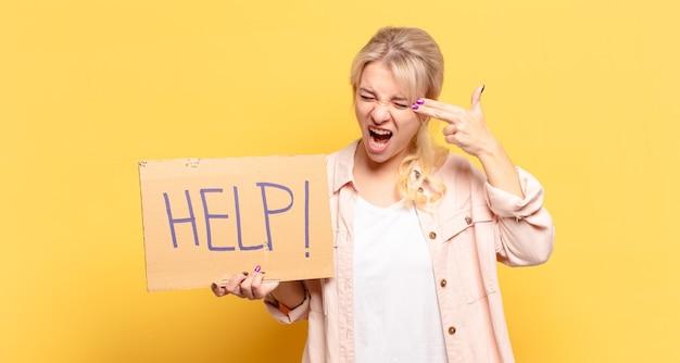 Blonde vrouw die ongelukkig en gestrest kijkt, zelfmoordgebaar maakt pistoolteken met hand, wijst naar hoofd