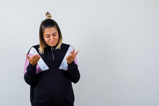 Blonde vrouw die ontevreden is over een domme vraag in een zwart trainingspak en er boos uitziet