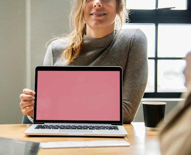 Blonde vrouw die op het laptop scherm richt