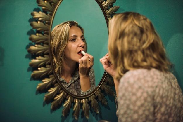 Blonde vrouw die op lippenstift zet