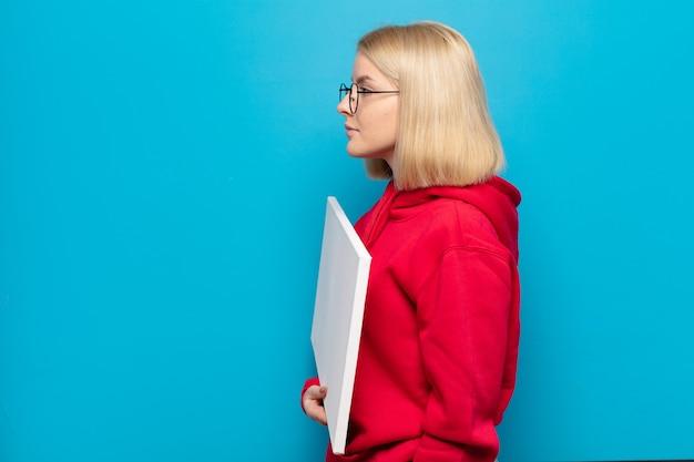 Blonde vrouw die op profielweergave ruimte vooruit wil kopiëren, denken, zich voorstellen of dagdromen