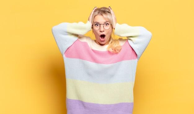 Blonde vrouw die opgewonden en verrast kijkt, met open mond en beide handen op het hoofd, voelt zich een gelukkige winnaar