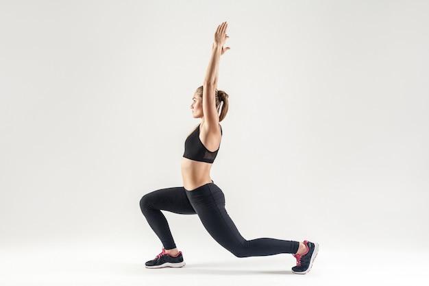 Blonde vrouw die pilates doet. profiel, zijaanzicht. studio opname, grijze achtergrond