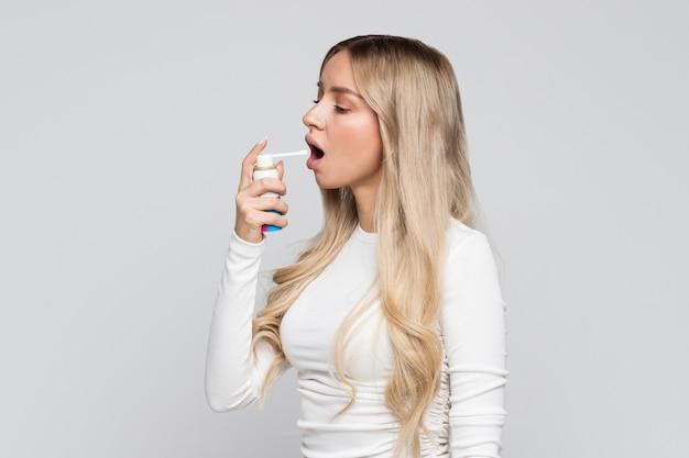 Blonde vrouw die spray gebruikt om keelpijn te behandelen.