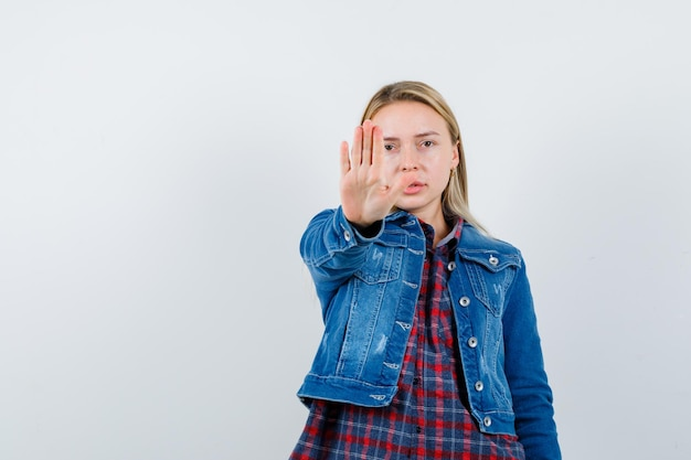 Blonde vrouw die stopgebaar in overhemd, jasje toont en resoluut kijkt.