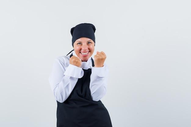 Blonde vrouw die succesgebaar in zwarte eenvormige kok toont en gelukkig kijkt. vooraanzicht.