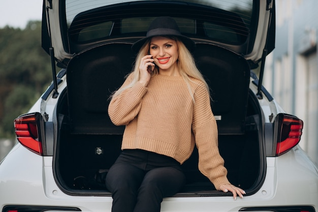 Blonde vrouw die telefoon gebruikt en in de kofferbak zit
