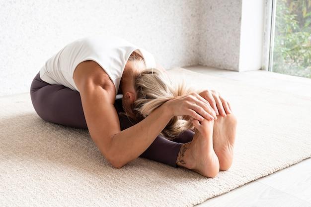 Blonde vrouw die thuis yoga beoefent die zich uitstrekt