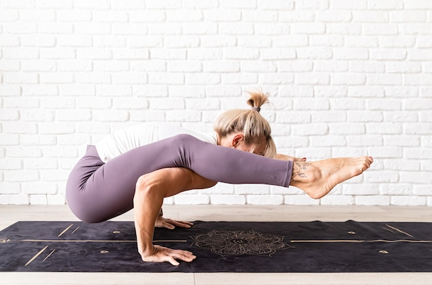 Blonde vrouw die thuis yoga beoefent en oefeningen maakt op de mat
