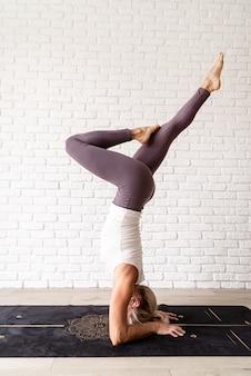 Blonde vrouw die thuis yoga beoefent met hoofdstand