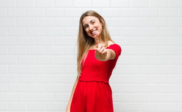 Blonde vrouw die trots en zelfverzekerd glimlacht en nummer één triomfantelijk poseert, voelt zich als een leider