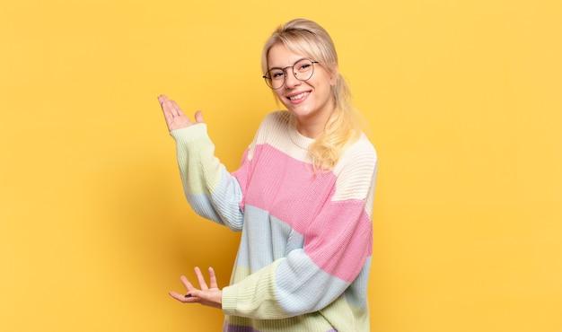 Blonde vrouw die trots en zelfverzekerd glimlacht, zich gelukkig en tevreden voelt en een concept op exemplaarruimte toont