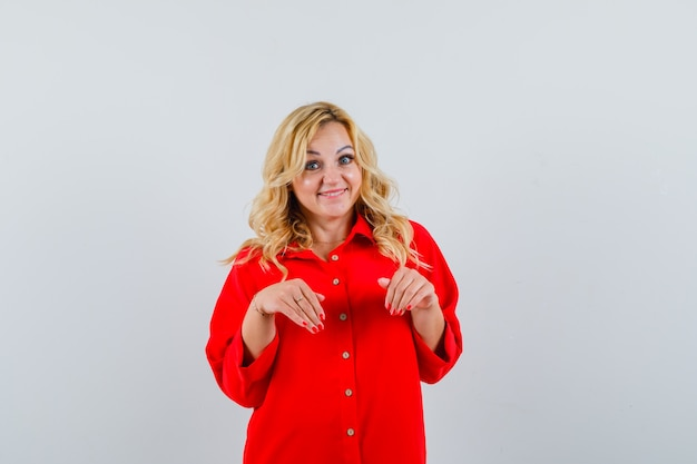 Blonde vrouw die uitnodigt om in rode blouse te komen en gelukkig, vooraanzicht kijkt.
