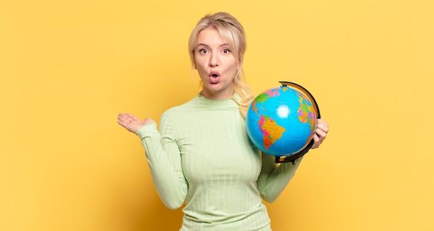 Blonde vrouw die verrast en geschokt kijkt, met open mond terwijl ze een object vasthoudt met een open hand aan de zijkant