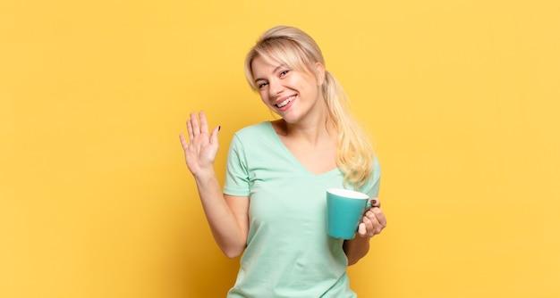 Blonde vrouw die vrolijk en opgewekt glimlacht, hand zwaait, je verwelkomt en begroet, of afscheid neemt