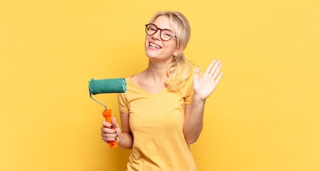 Blonde vrouw die vrolijk en opgewekt glimlacht, hand zwaait, u verwelkomt en begroet, of afscheid neemt