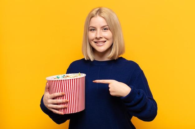 Blonde vrouw die vrolijk glimlacht, zich gelukkig voelt en naar de zijkant en naar boven wijst, voorwerp in exemplaarruimte toont