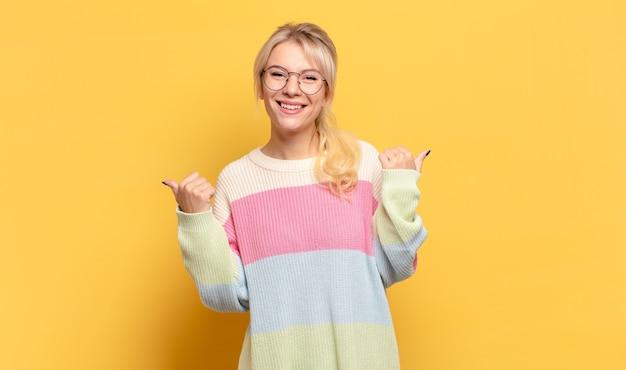 Blonde vrouw die vrolijk lacht en er gelukkig uitziet, zich zorgeloos en positief voelt met beide duimen omhoog