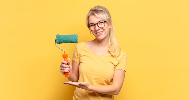 Blonde vrouw die vrolijk lacht, zich gelukkig voelt en een concept in kopieerruimte toont met handpalm