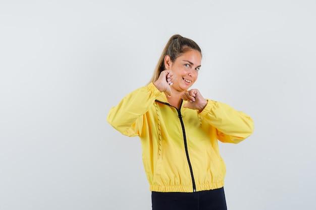 Blonde vrouw die vuisten in geel bomberjack en zwarte broek balde en gelukkig kijkt