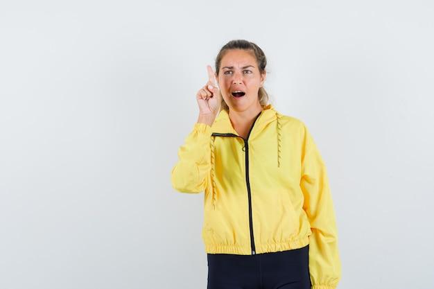Blonde vrouw die wijsvinger in eureka-gebaar in geel bomberjack en zwarte broek opheft en verbaasd kijkt